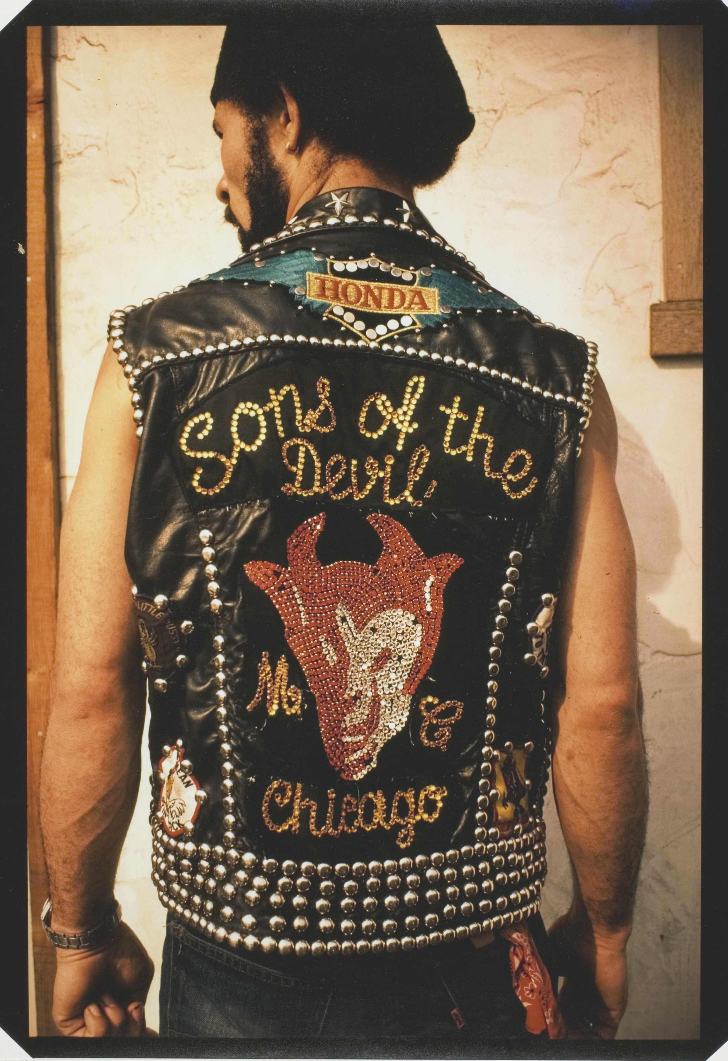 """A man poses with his back to the camera in a motorcycle vest emblazoned with sequins reading """"Sons of the Devil MC Chicago"""""""