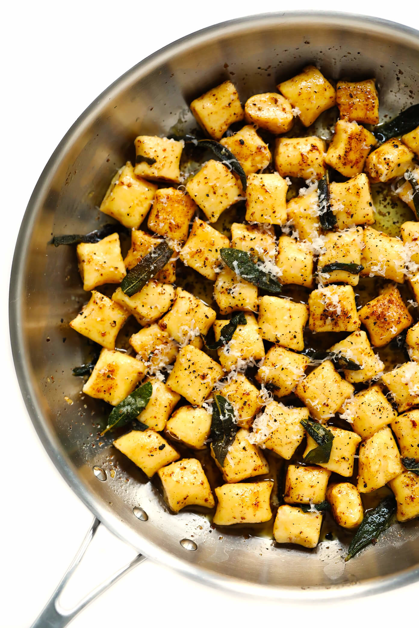 Skillet filled with ricotta gnocchi tossed with fried herbs, grated parmesan cheese, and butter.