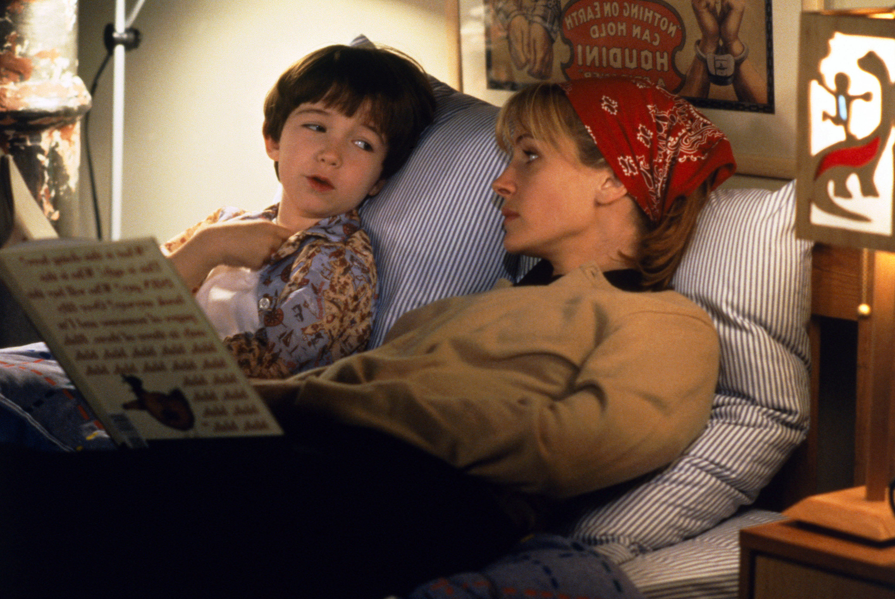 Julia Roberts in character reads a book to her fictional child in bed
