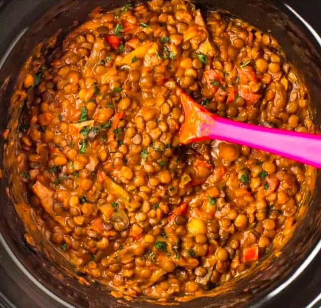 Big spoon stirring a pot of cheesy lentils
