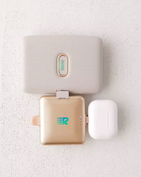 A flatlay of a three-pronged charger powering up two devices at the same time