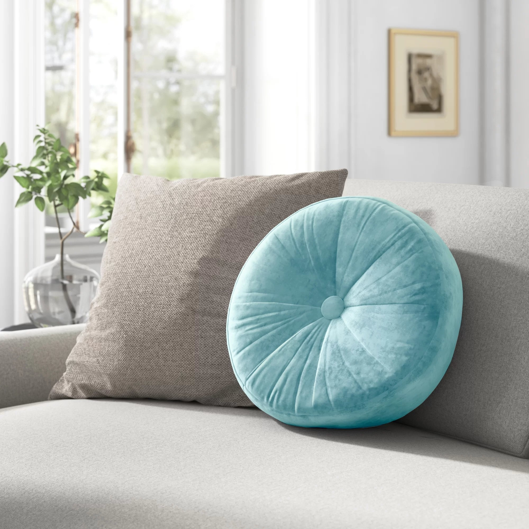 The round pillow with a button in the center on a couch