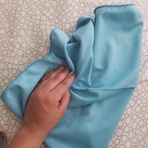 a reviewer wiping a surface with one of the cloths