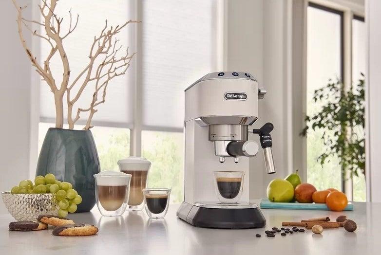 The white espresso maker on a kitchen counter making a cup of espresso