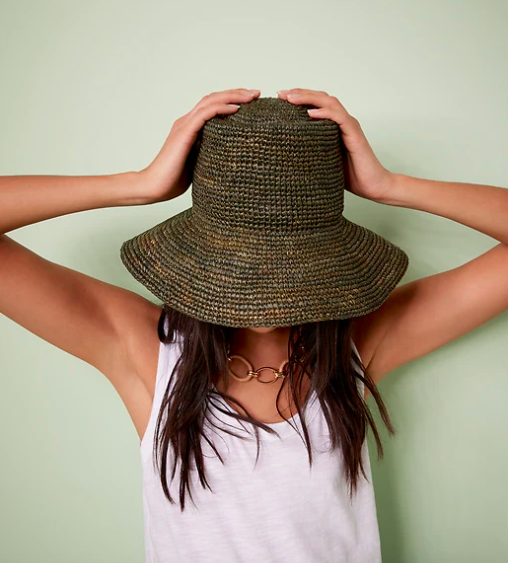 A person wearing the straw hat with a tank top