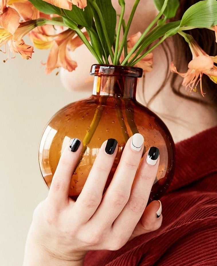 model holding a flower pot and showing black and white nails