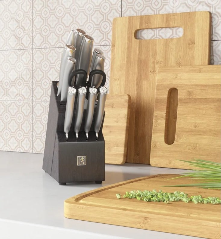 The stainless steel knife set in a black knife block on a kitchen counter next to a bamboo cutting board