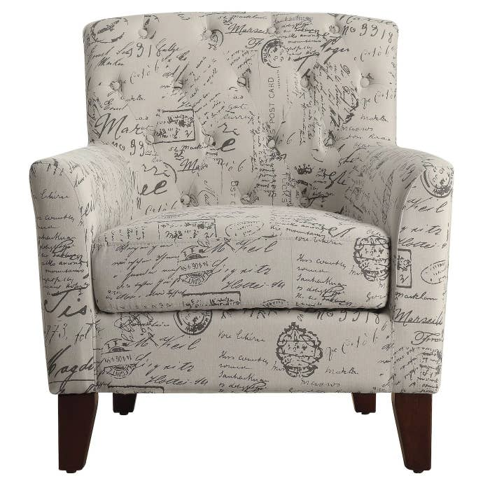 The chair with script pattern, a tufted back and plush seat with dark wooden legs