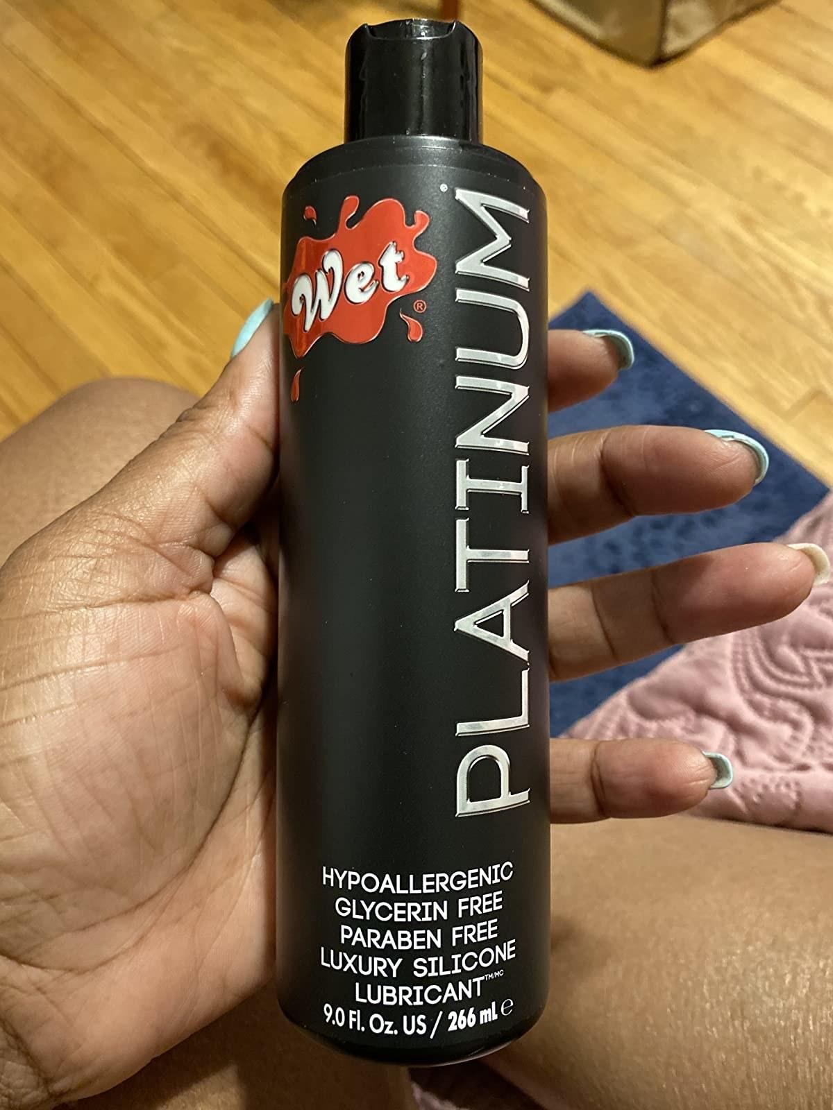 Model holding black bottle of Wet Platinum lubricant