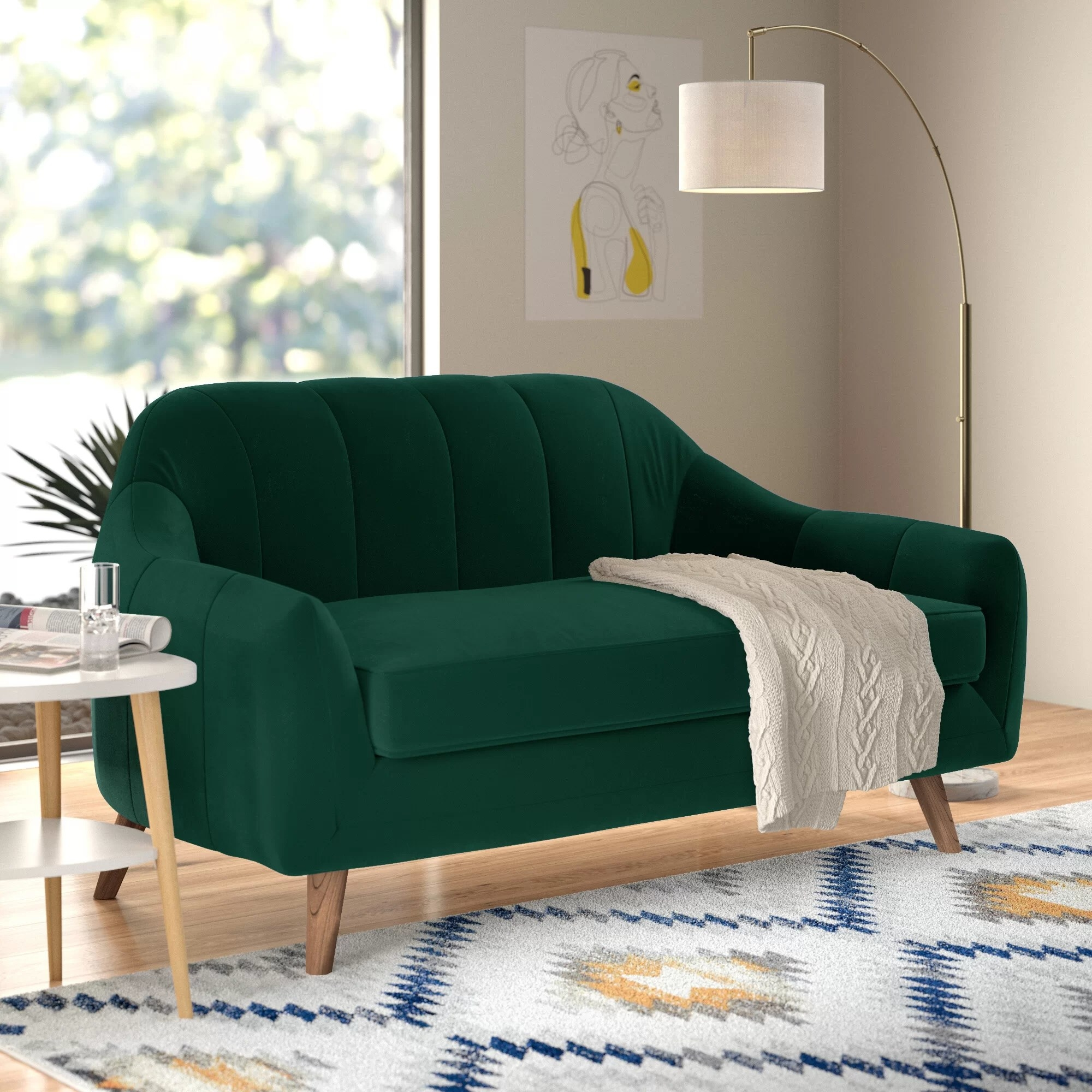 The forest green loveseat with vertical tufting, and flared arms and legs in a living room