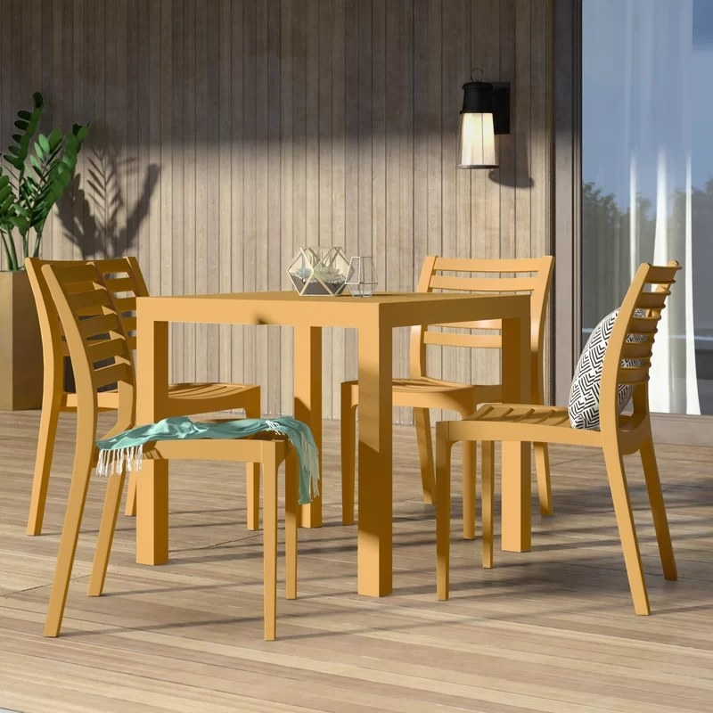 The dining set in a light wood color with four chairs and a square table on an outdoor deck