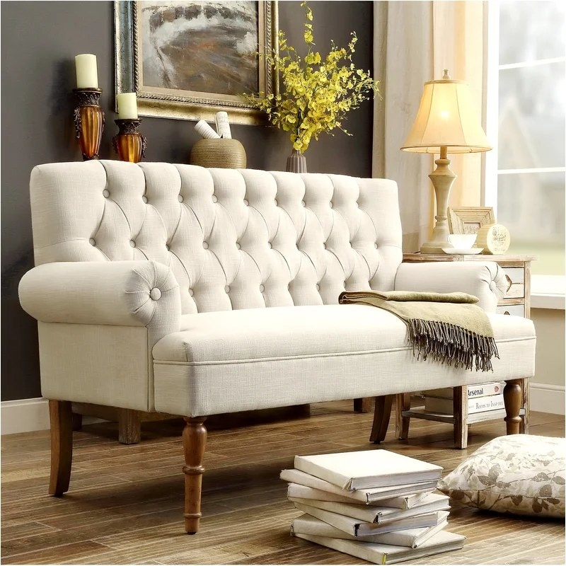 The settee with a tufted back, rolled arms, and wooden legs in a living room