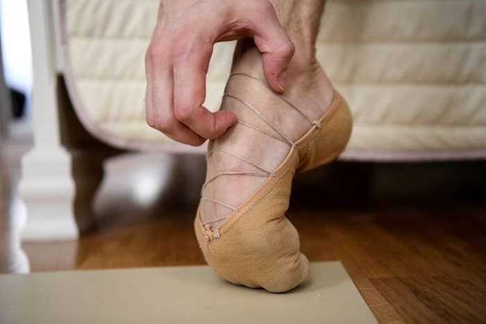 A ballet shoe on a pointed and bent foot