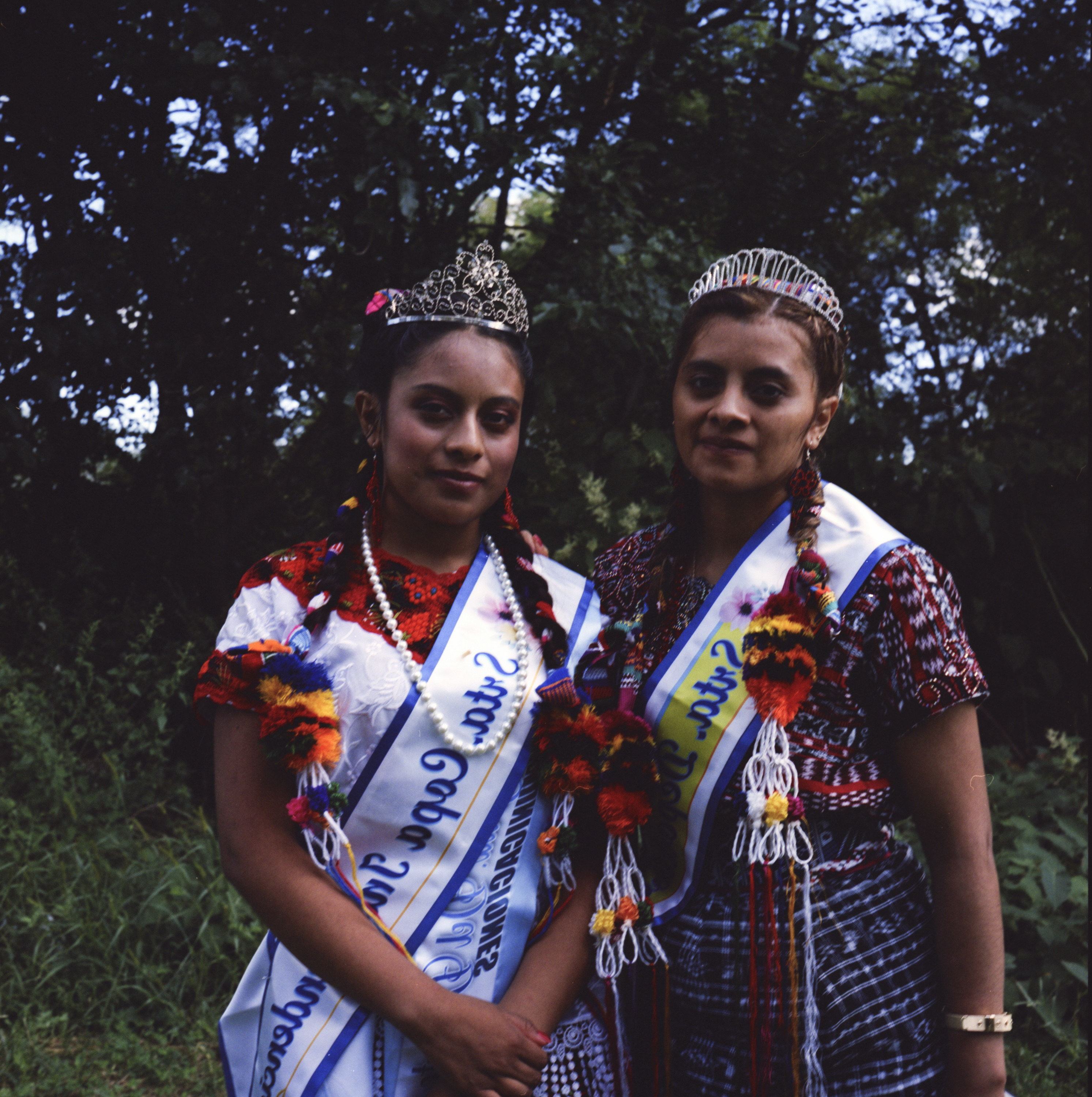 Two women in Indigenous clothing, tiaras, and sashes in front of greenery