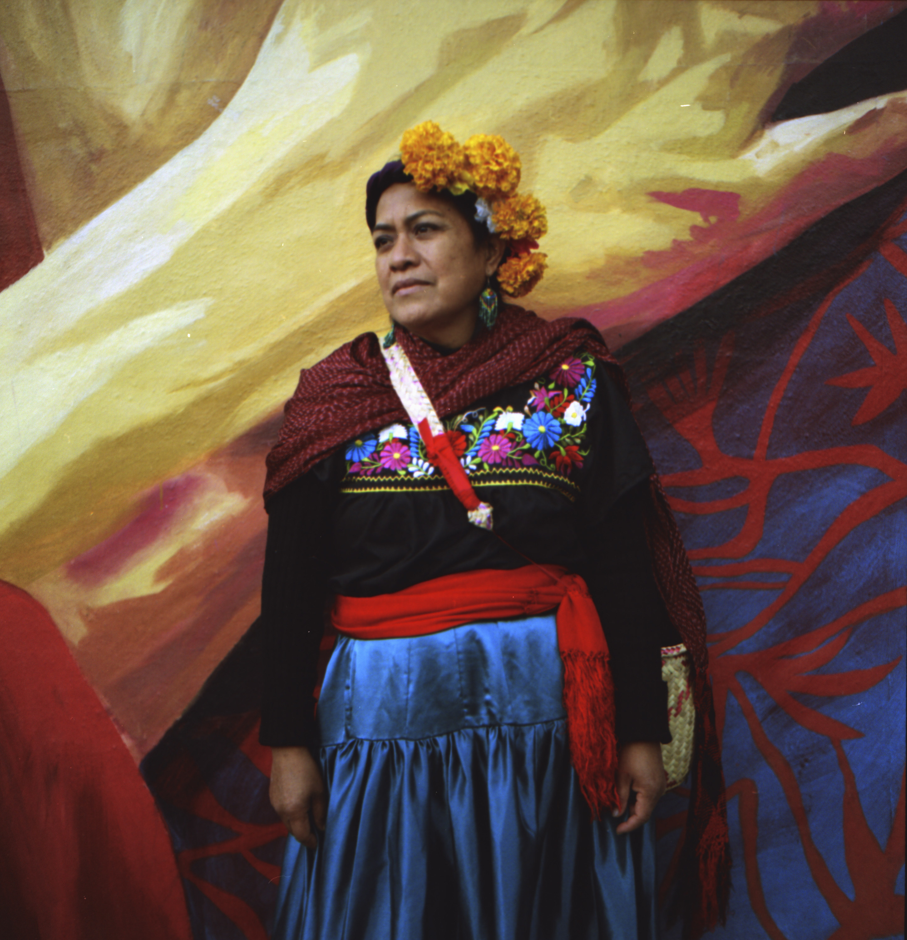 An indigenous Mexican woman with a flower crown standing in front of a mural