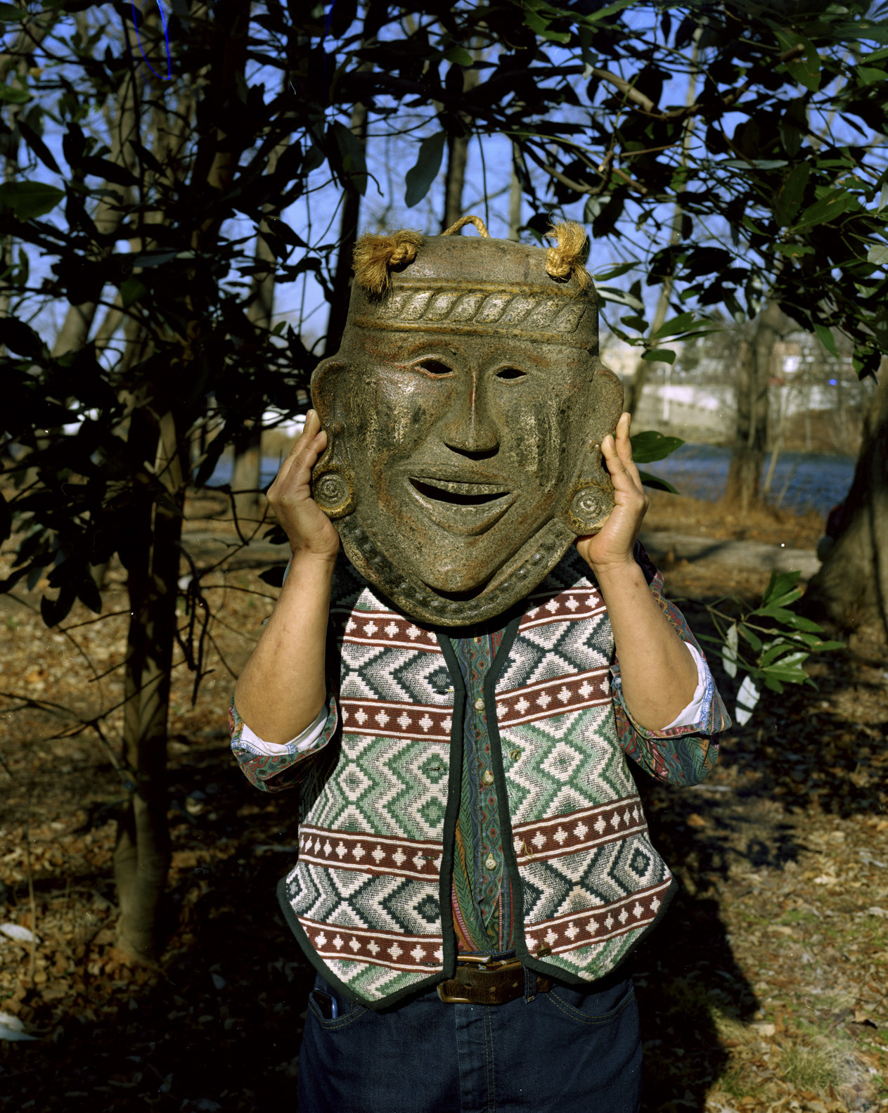 A man holding up a large replica of an Indigenous clay mask to this face