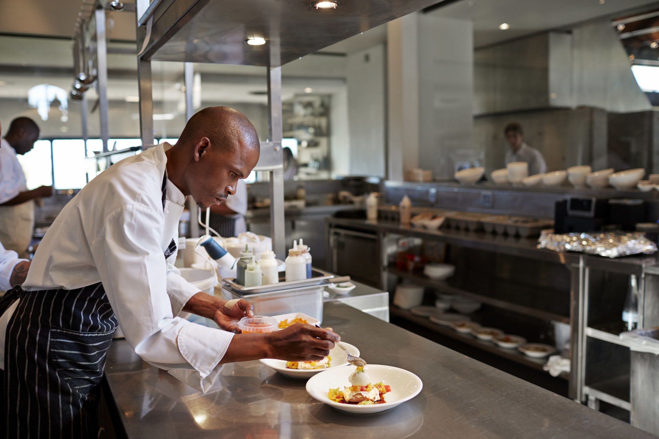 A chef sprucing up a dish in the kitchen
