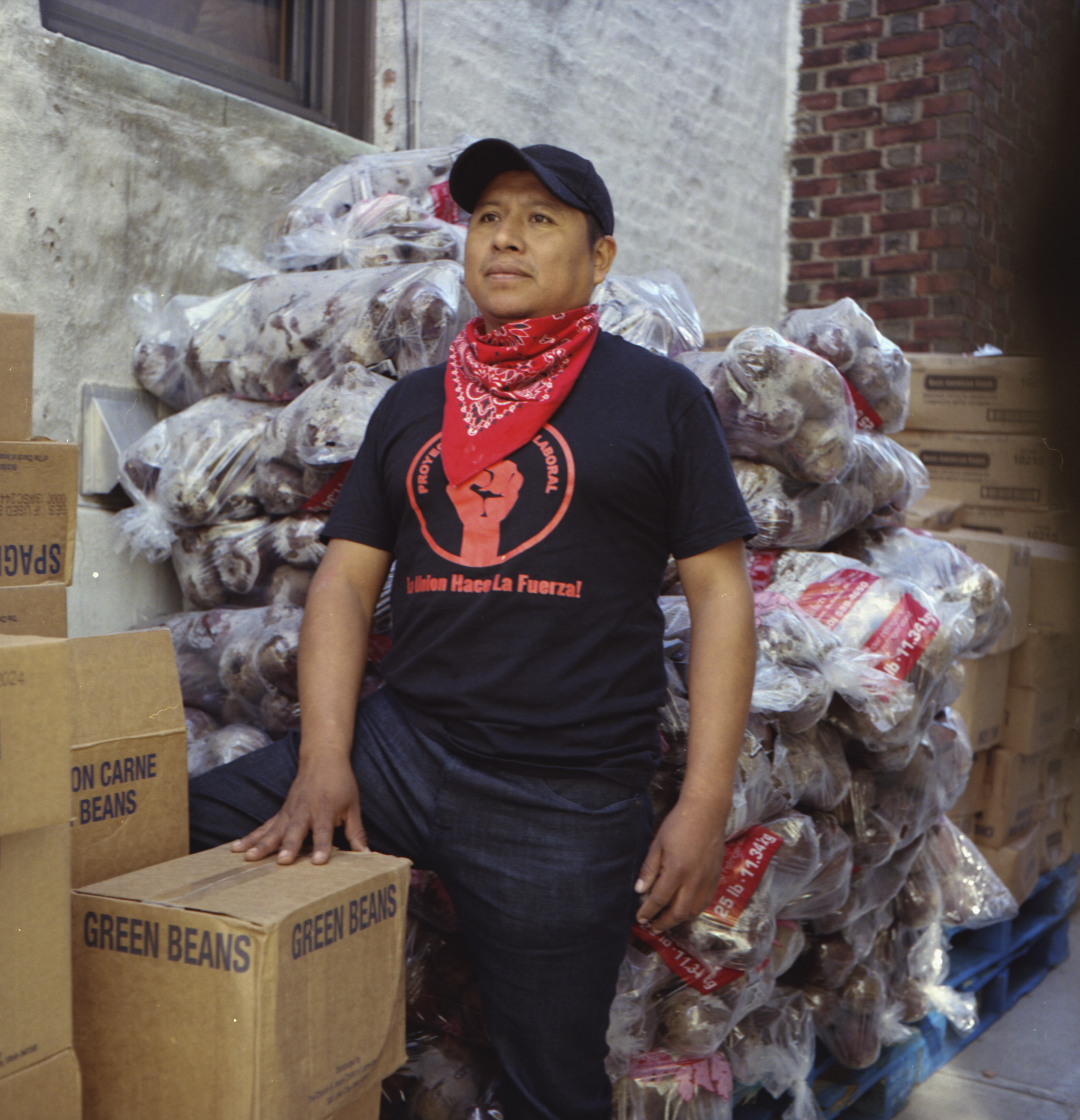 A man with a bandana around his neck in front of a box of green beans and piles of food