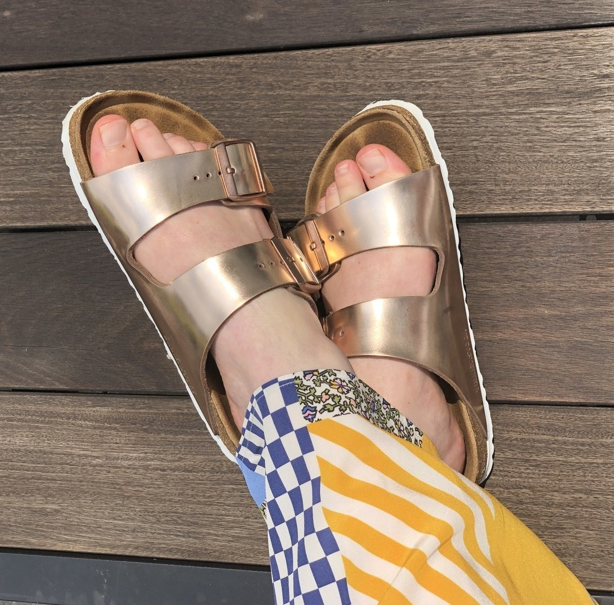 Natalie's feet with two-strap flat sandal with a big shiny buckle on each strap, in shiny copper