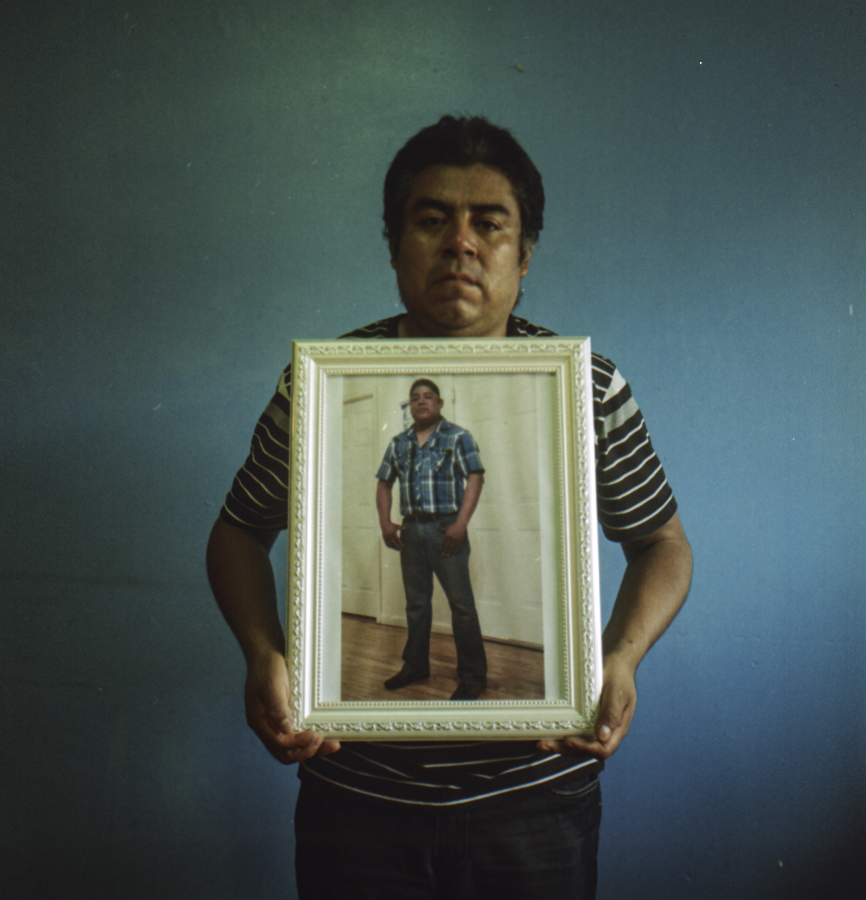 A man holding a framed portrait of his brother on a blue wall background