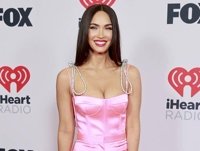 Megan smiles while wearing a pink silk corset top