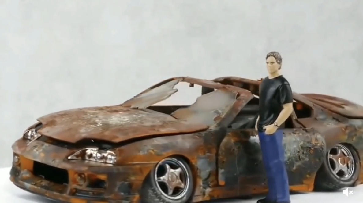 A beat-up toy car that's rusted and has broken windows