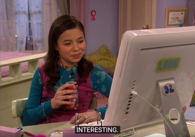 Megan looking at her desktop computer while holding a can of Coke