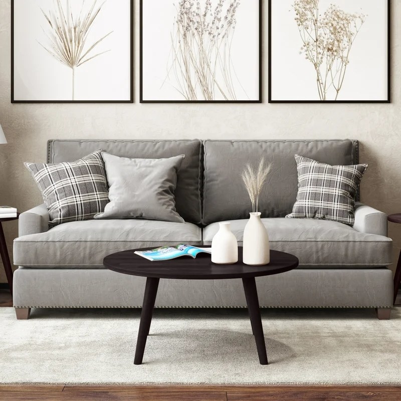 The espresso brown round coffee table with flared legs in a living room