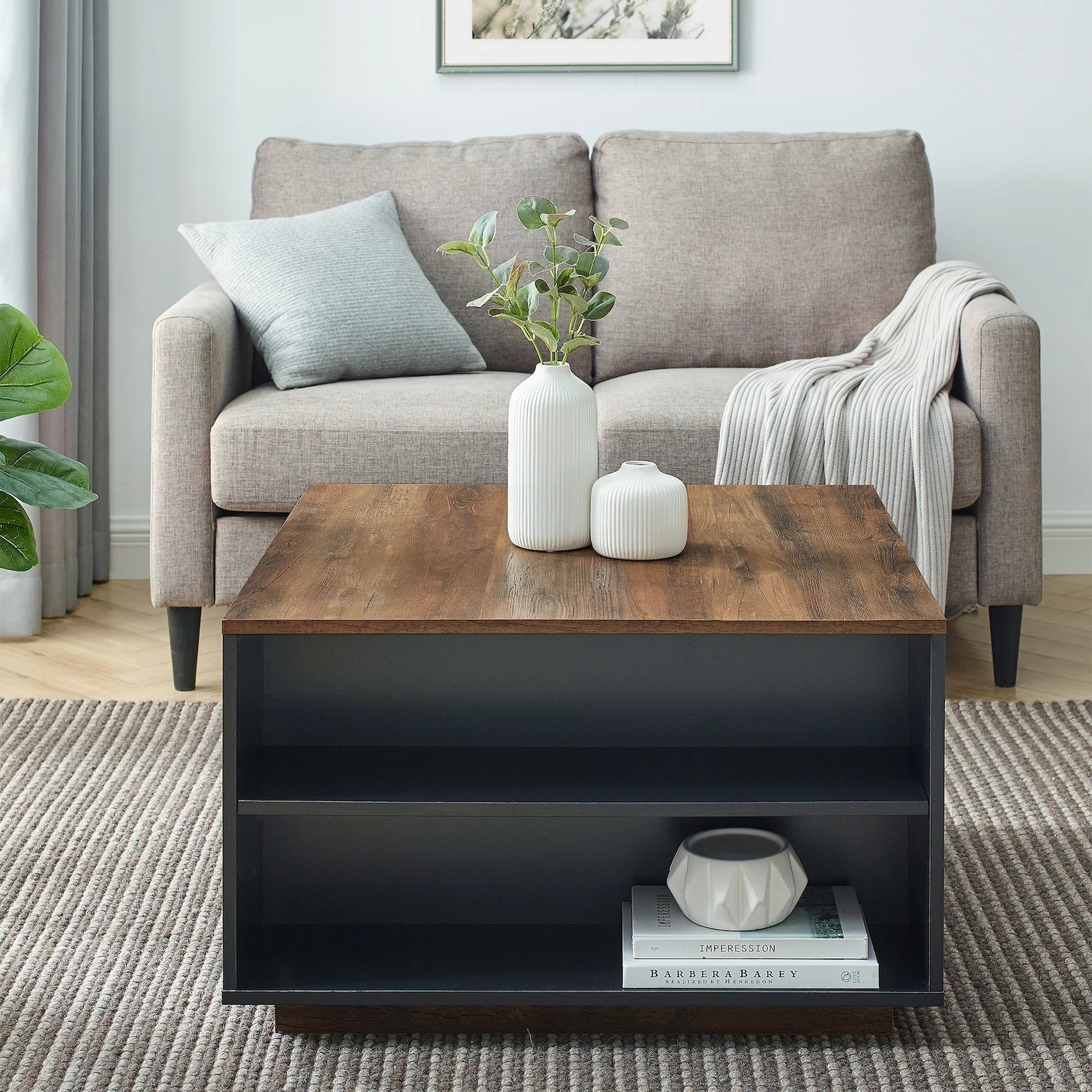 The coffee table with a black base and brown top, as well as two visible open shelves, in a living room