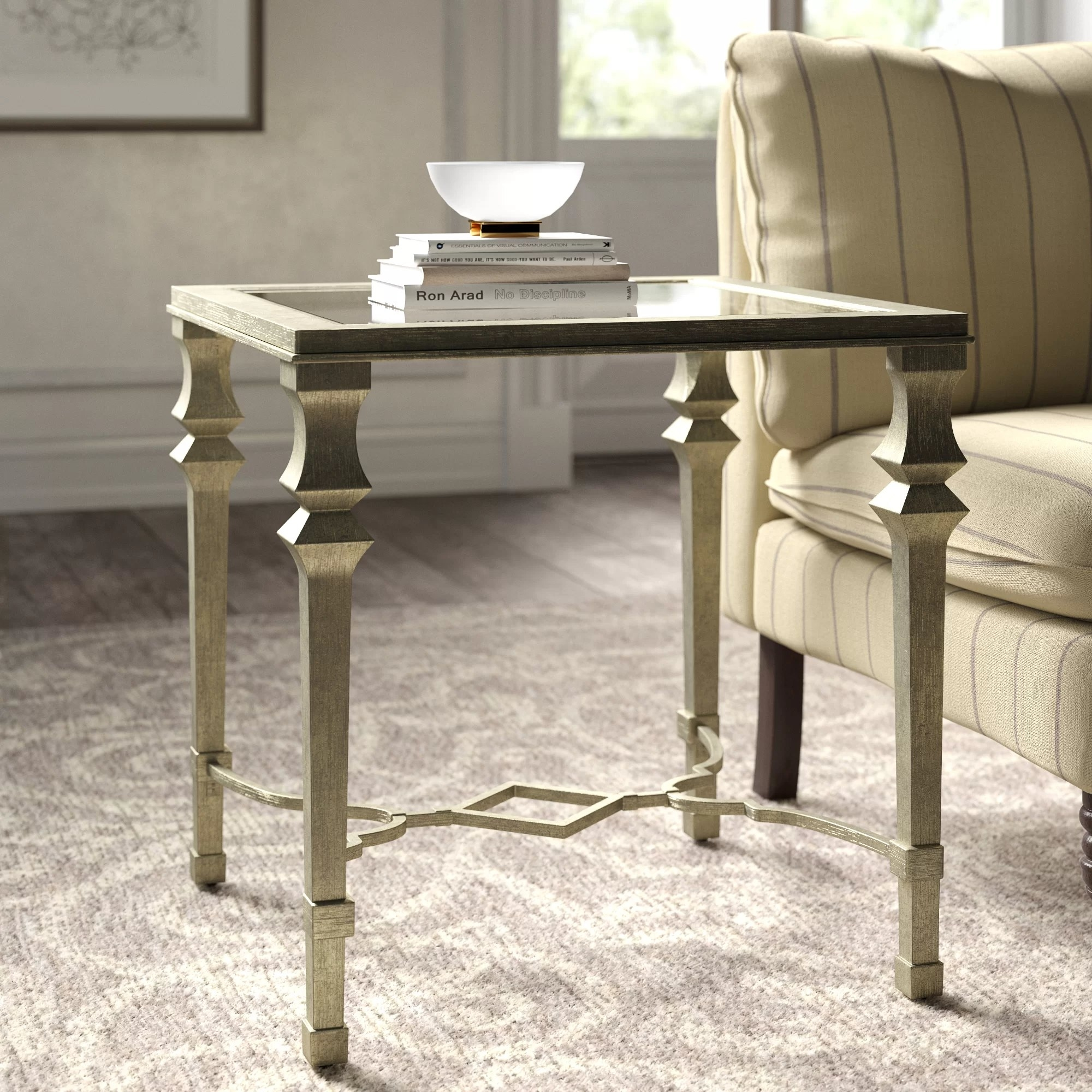 The square end table with a glass surface, silver frame and a cross design near the base in a living room