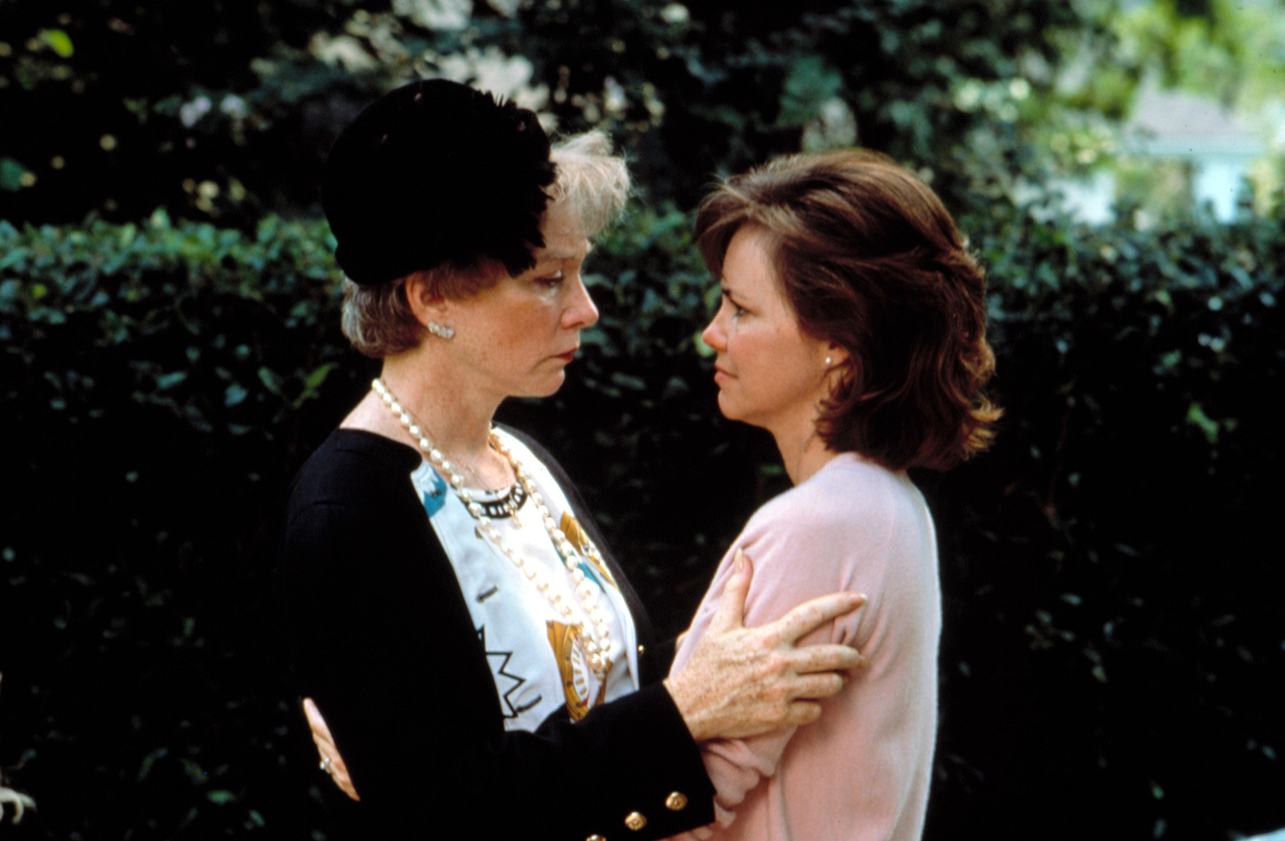 Shirley MacLaine and Sally Field embrace at a sad event