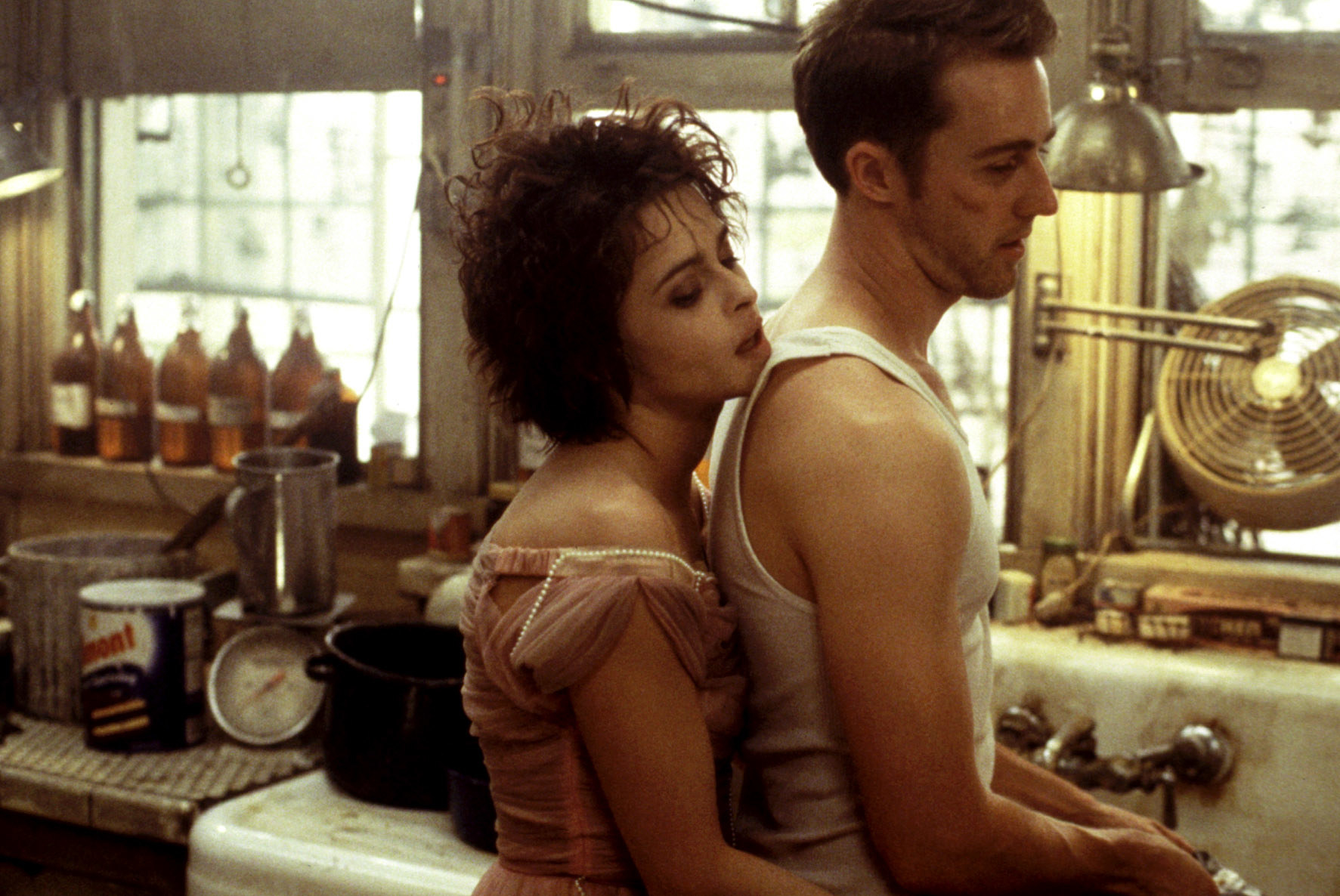 Helena Bonham Carter hugging Edward Norton from behind in a kitchen
