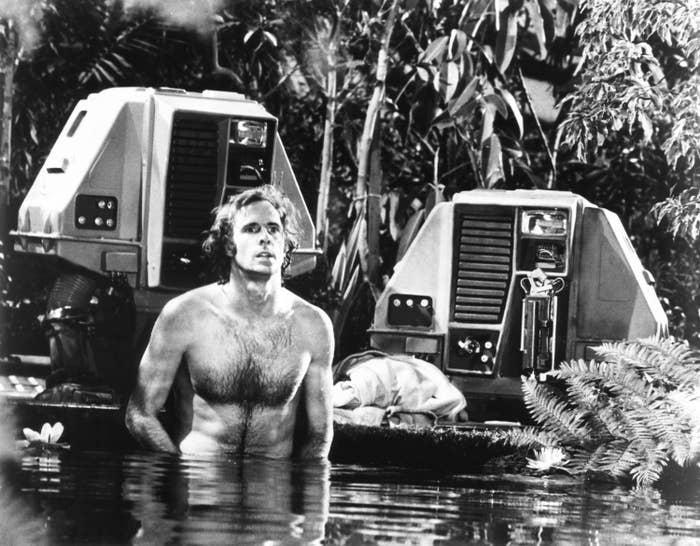 Bruce Dern walking through a lake near a space vehicle