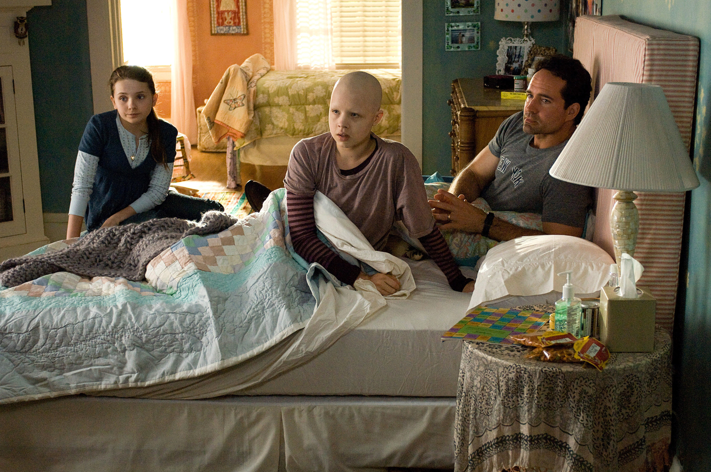 An adult, a child with cancer, and another child sit on a bed