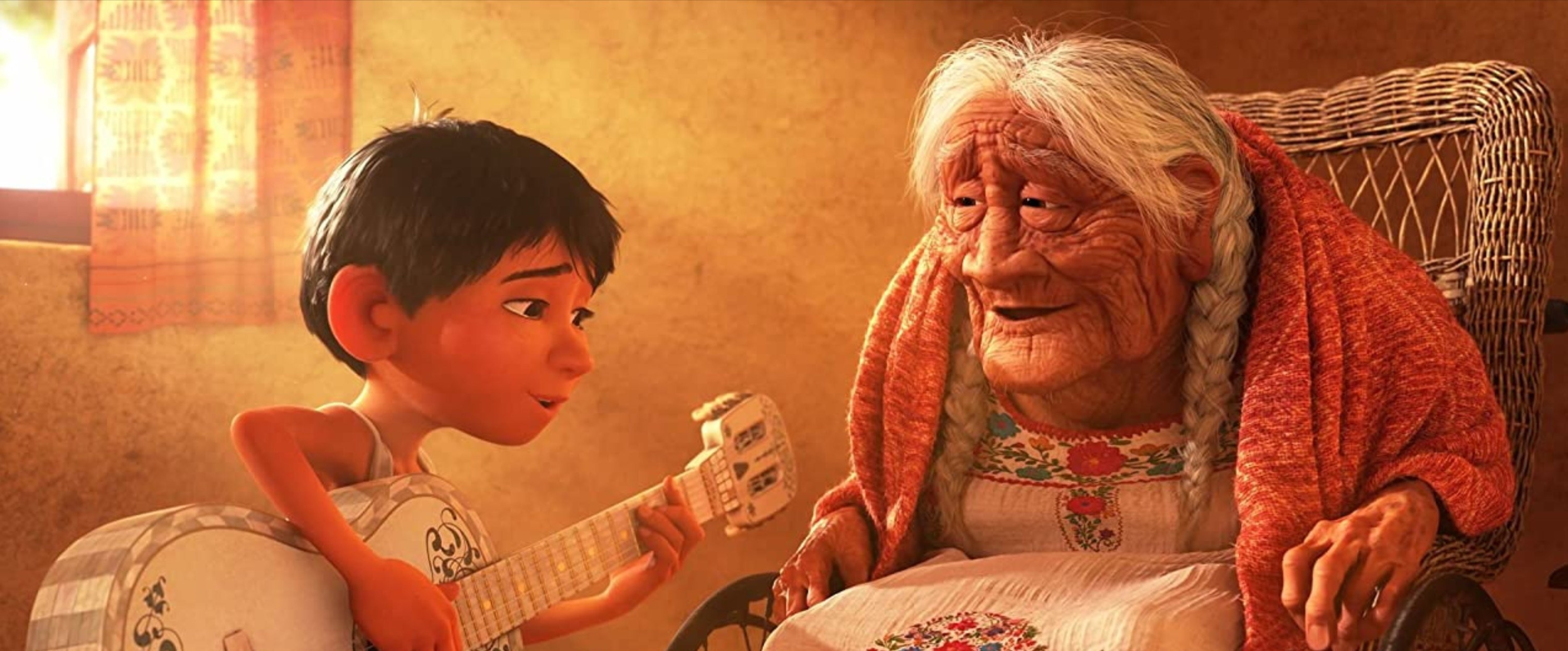 Miguel playing the guitar and singing to Mama Coco