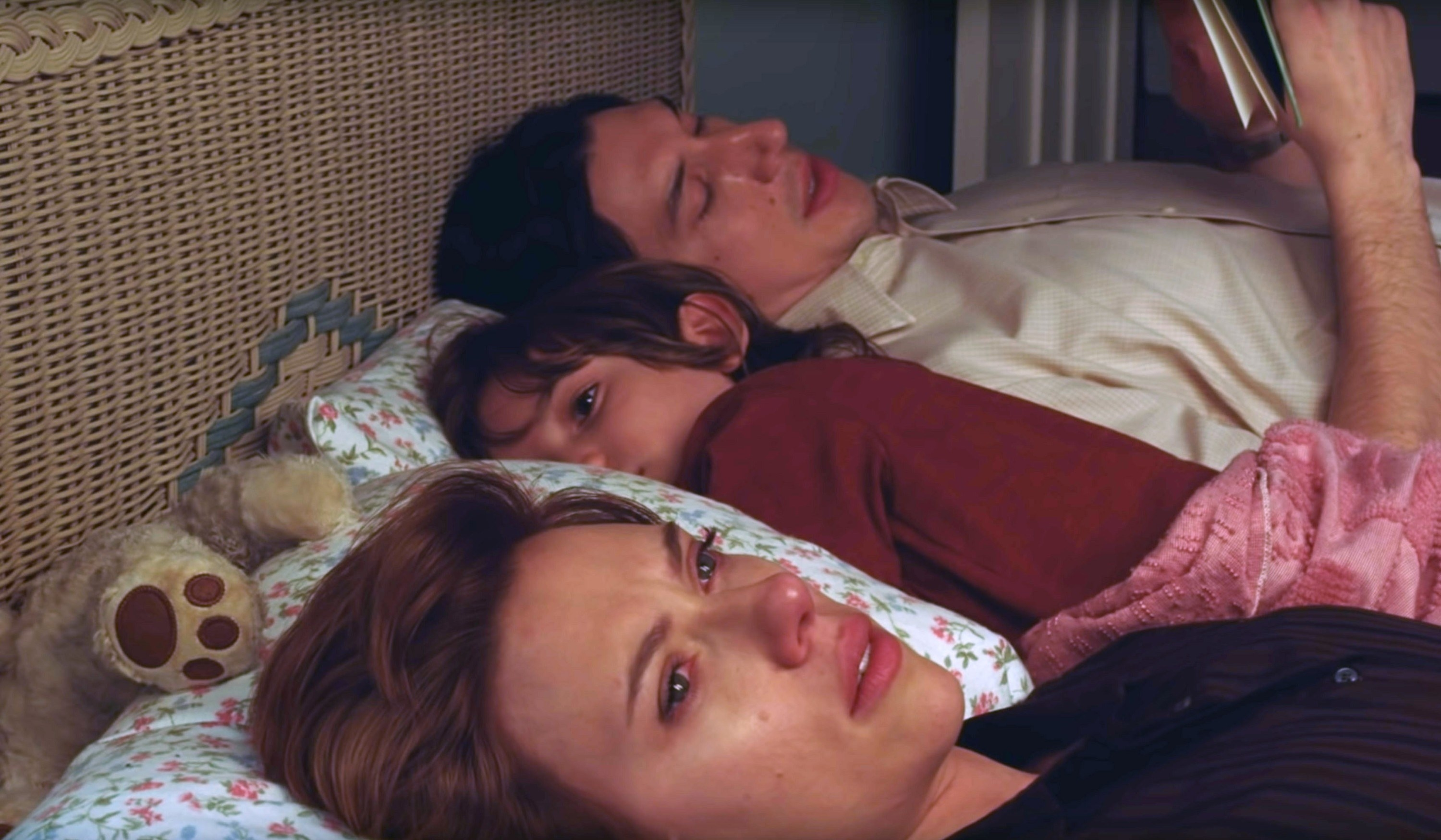 Scarlet Johansson in character lays in bed next to her kid and husband looking sad