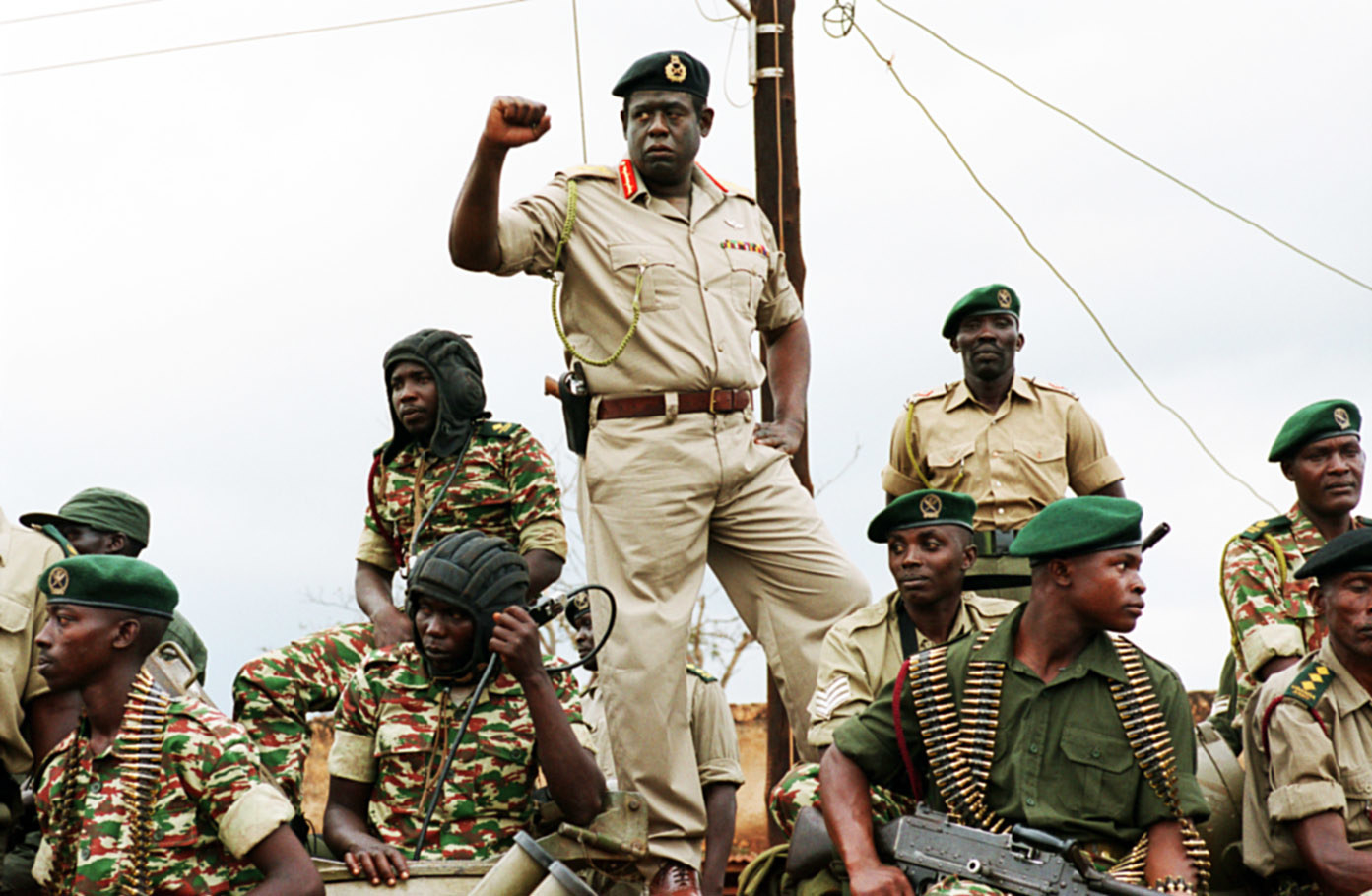 Forest Whitaker as Idi Amin standing among soldiers with his fist in the air
