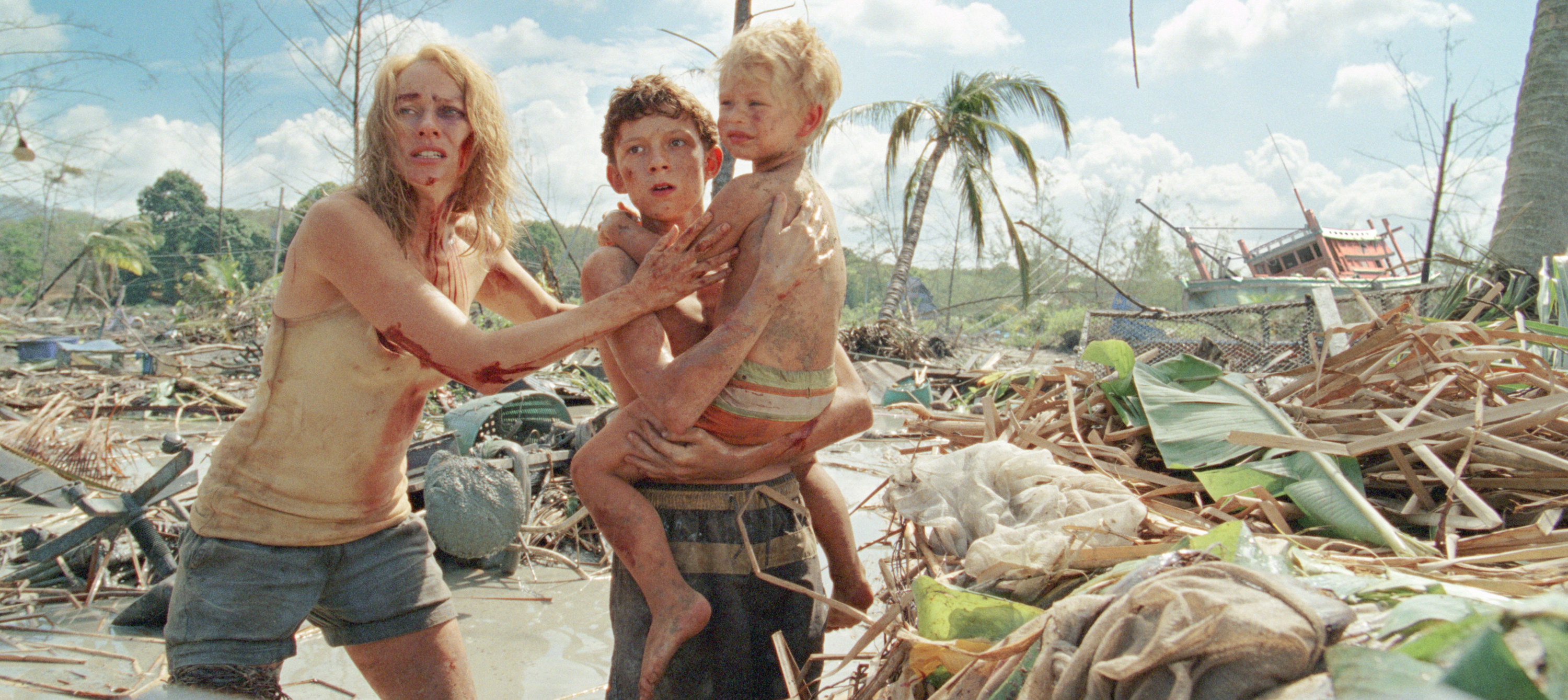 Naomi Watts and Tom Holland in character bleeding and climbing out of debris and water