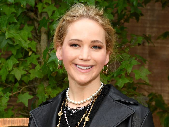 Jennifer smiles while wearing a black moto leather jacket and layered necklaces