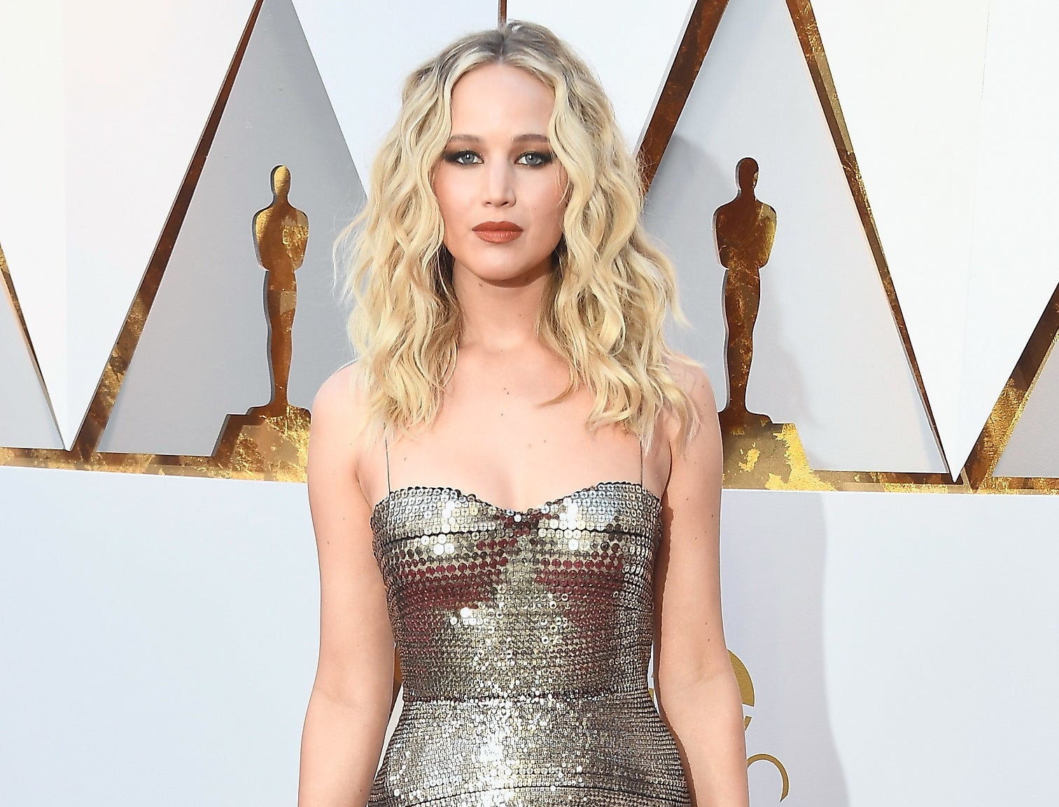 Jennifer wears a silver sequined gown