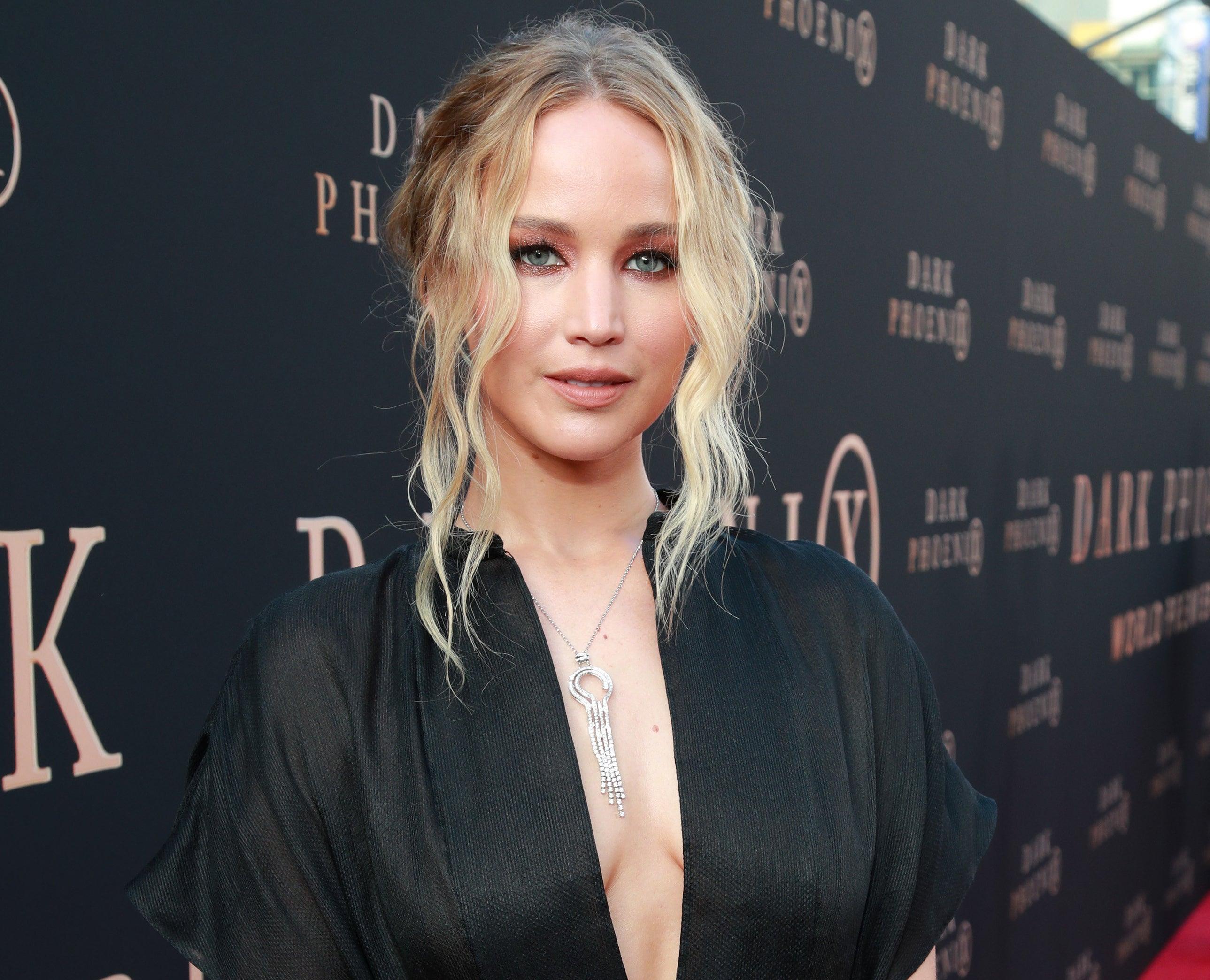Jennifer wears a black dress with a plunging neckline