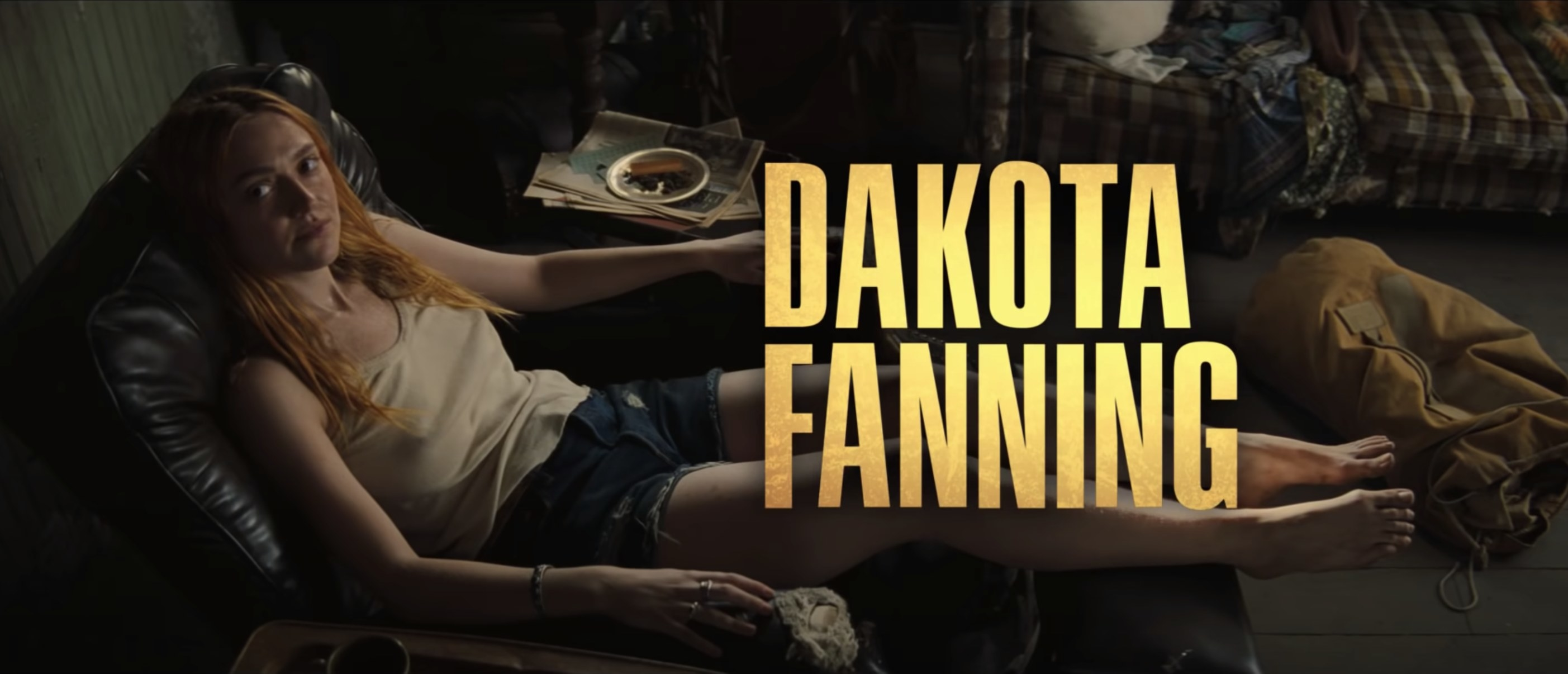 Dakota sits on a reclining chair in a screenshot from the movie