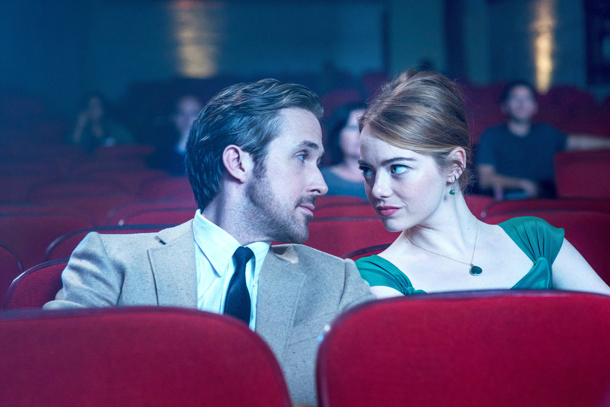 Ryan Gosling and Emma Stone looking at each other in a movie theater
