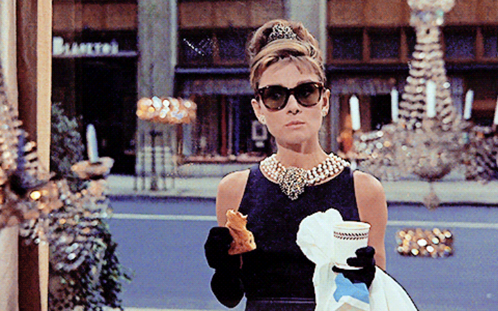 Holly Golightly/Audrey Hepburn eating a croissant and looking at the Tiffany's window