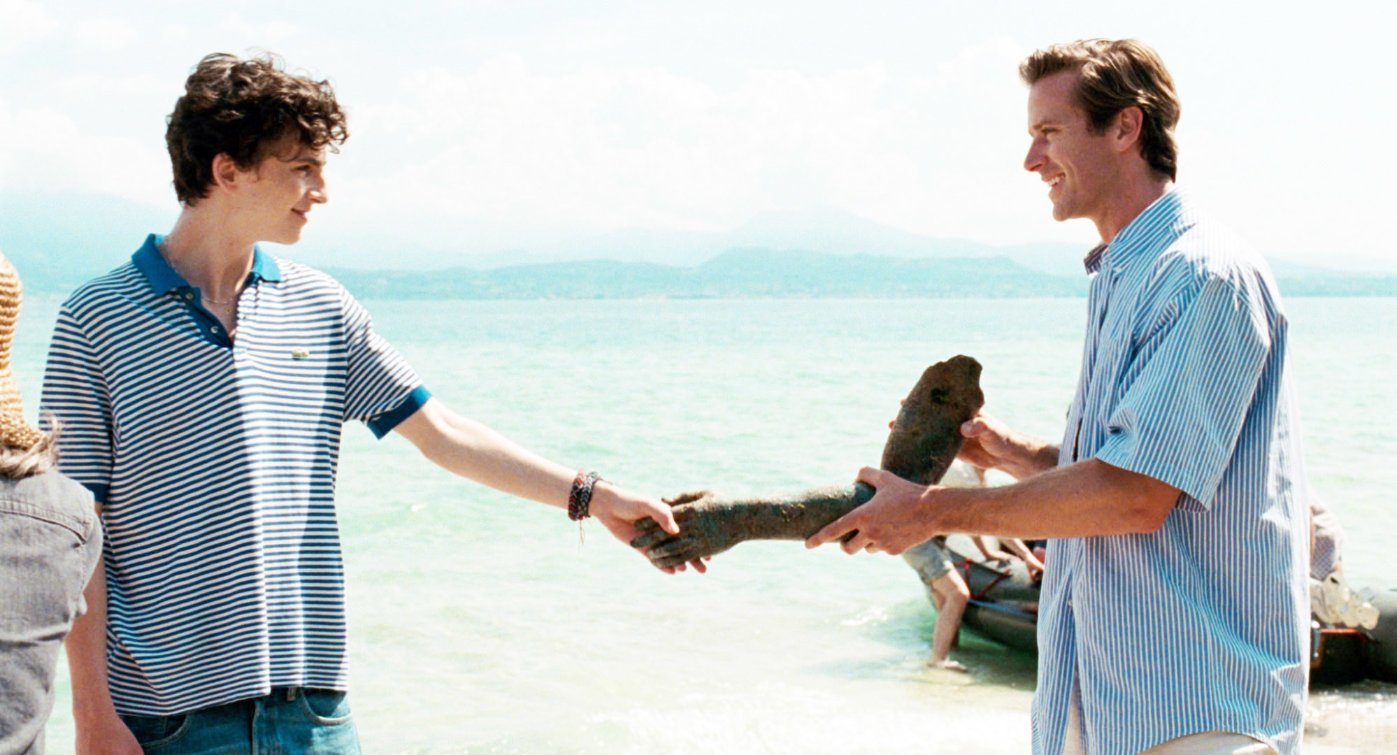Elio and Oliver pretending to shake hands with a rock hand