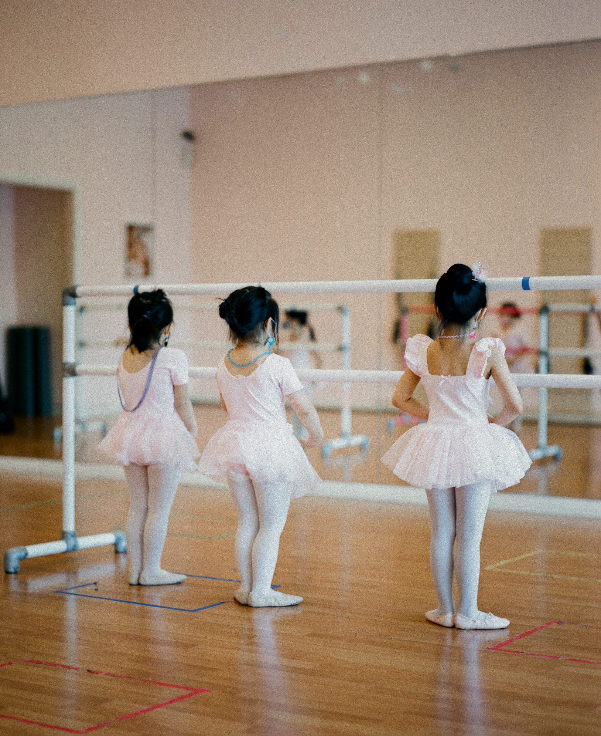 Three young girls in ballet costumes in a classroom