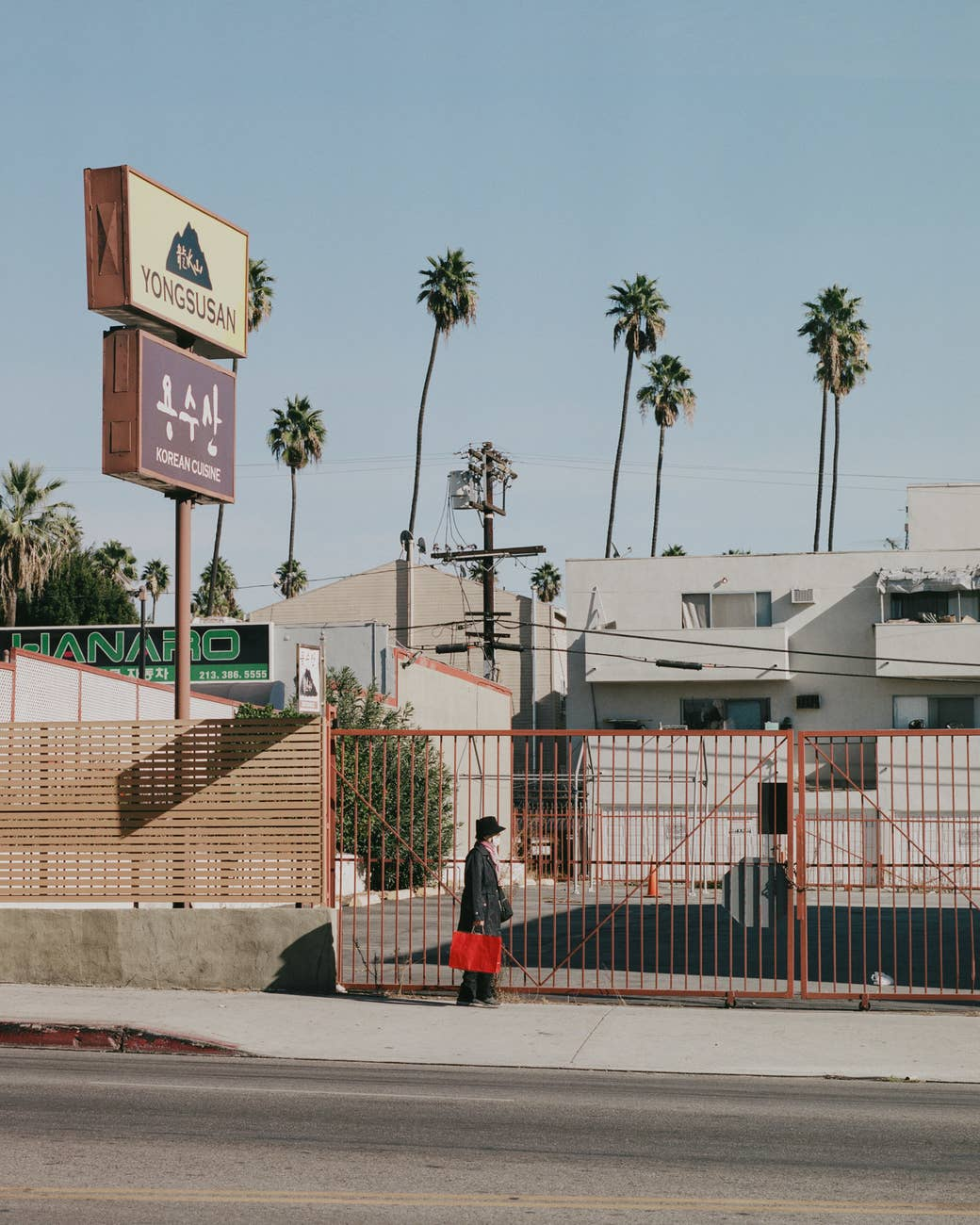 A woman with a red bag walks by a gate in Koreatown