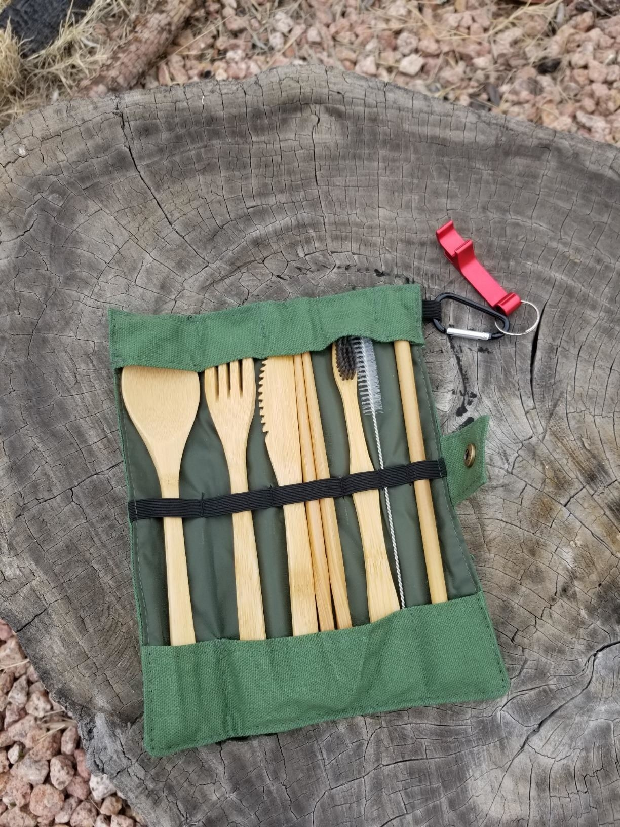 the bamboo cutlery set in a green case on a tree stump