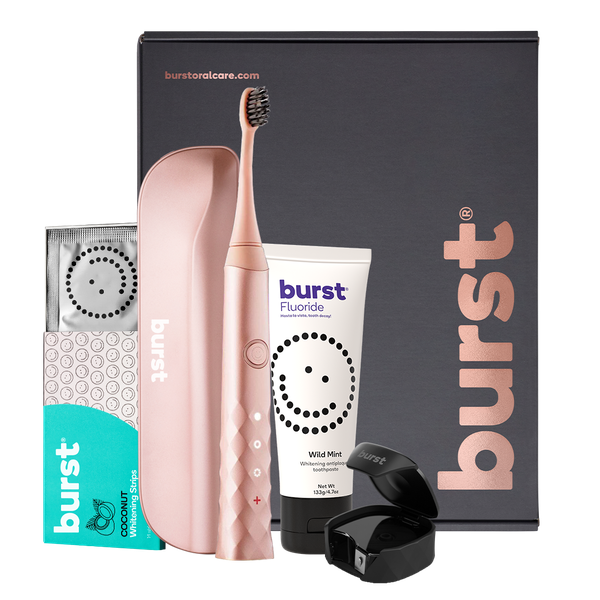 a rose gold tooth brush and dental accessories