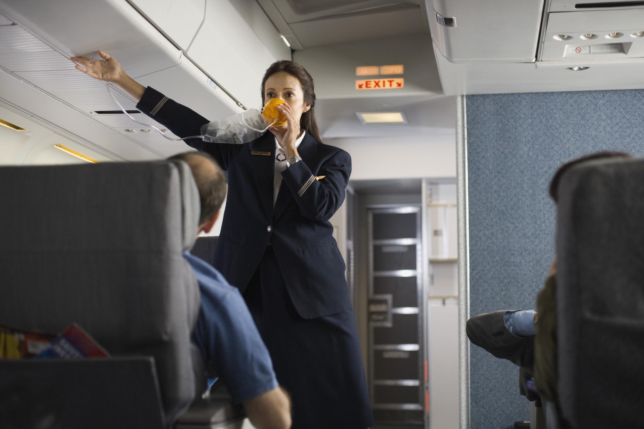 A flight attendant demonstrating the oxygen mask